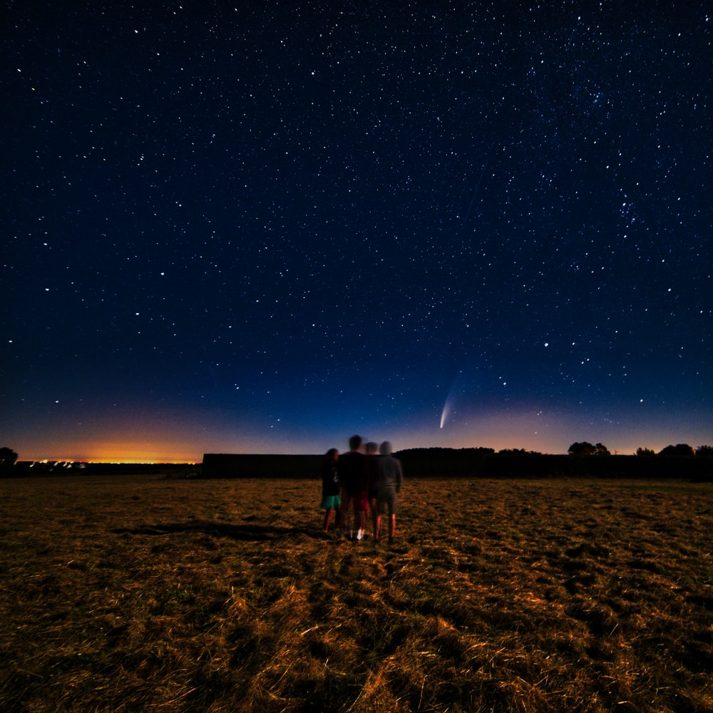 people standing on brown field under blue sky during night time