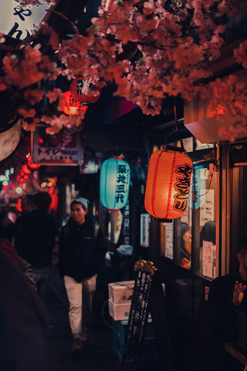 people standing near red paper lantern during nighttime