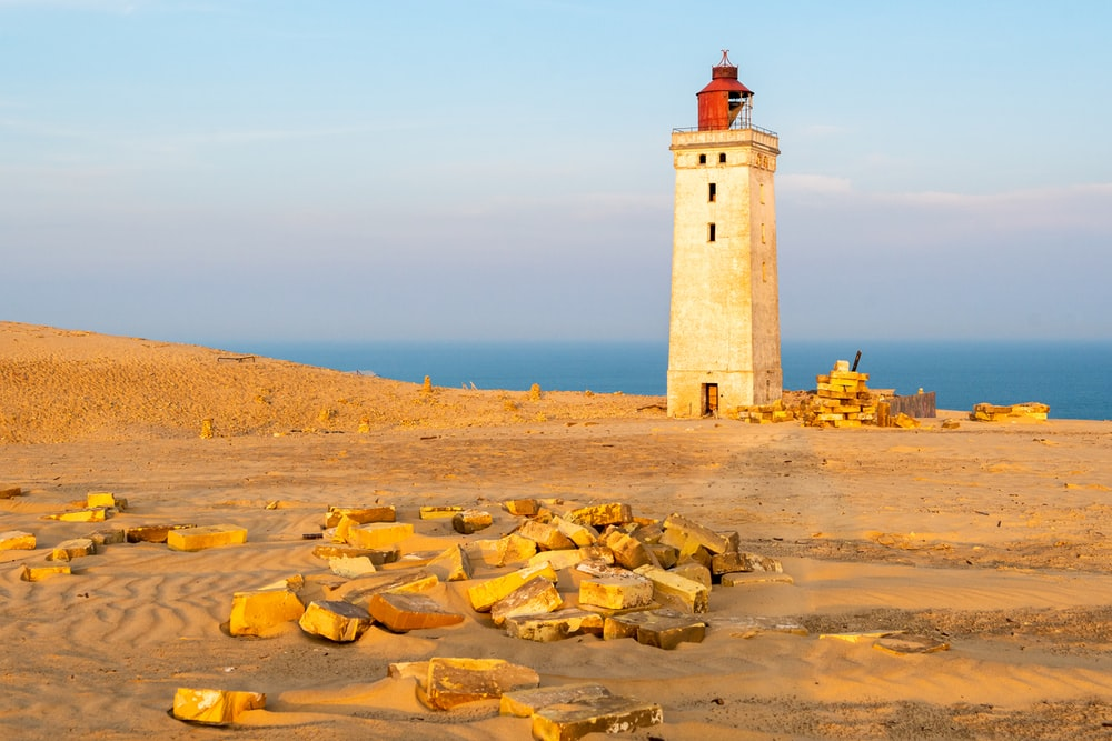 white and brown lighthouse on brown sand near body of water during daytime