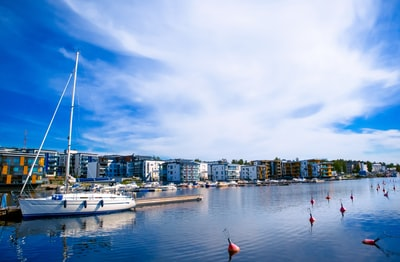 white and red boat on sea near city buildings under blue and white sunny cloudy sky finland zoom background