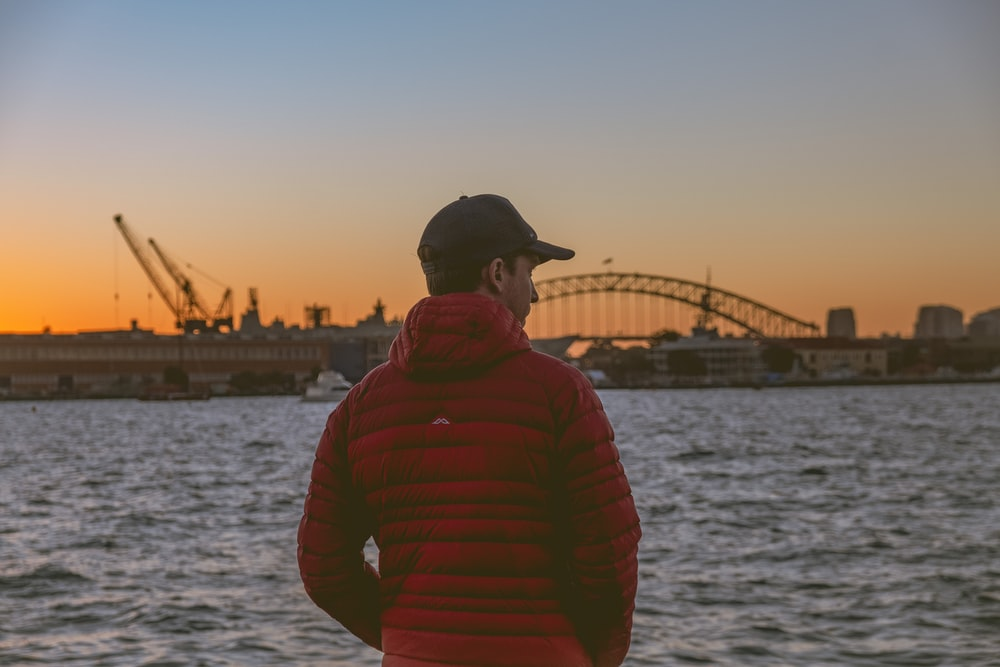 man in red hoodie standing near body of water during daytime