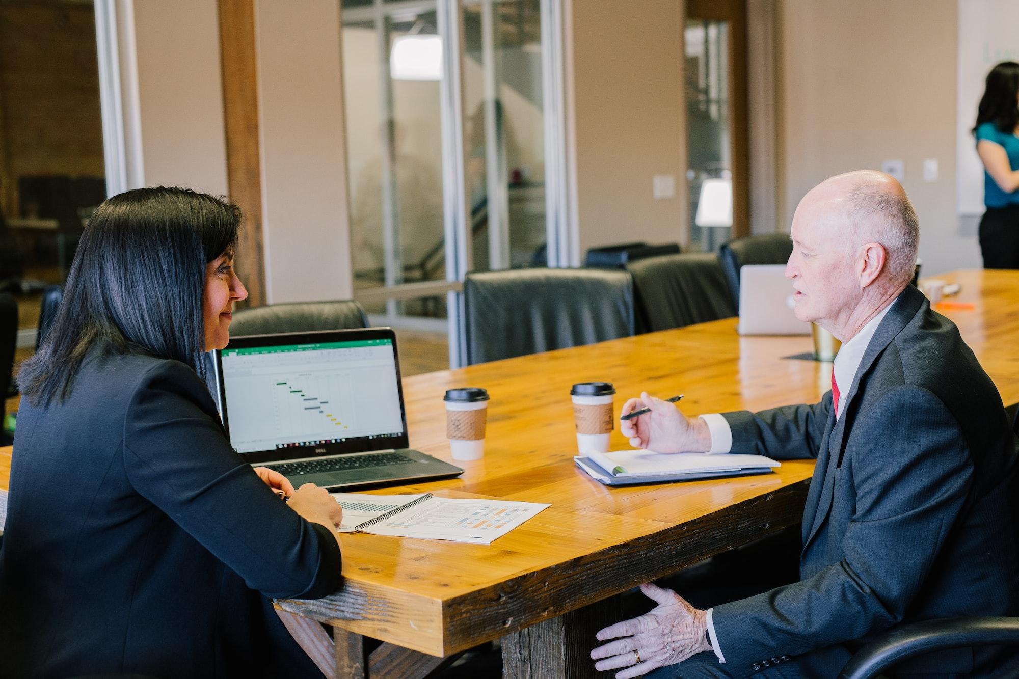 Woman boss educating older gentleman working together