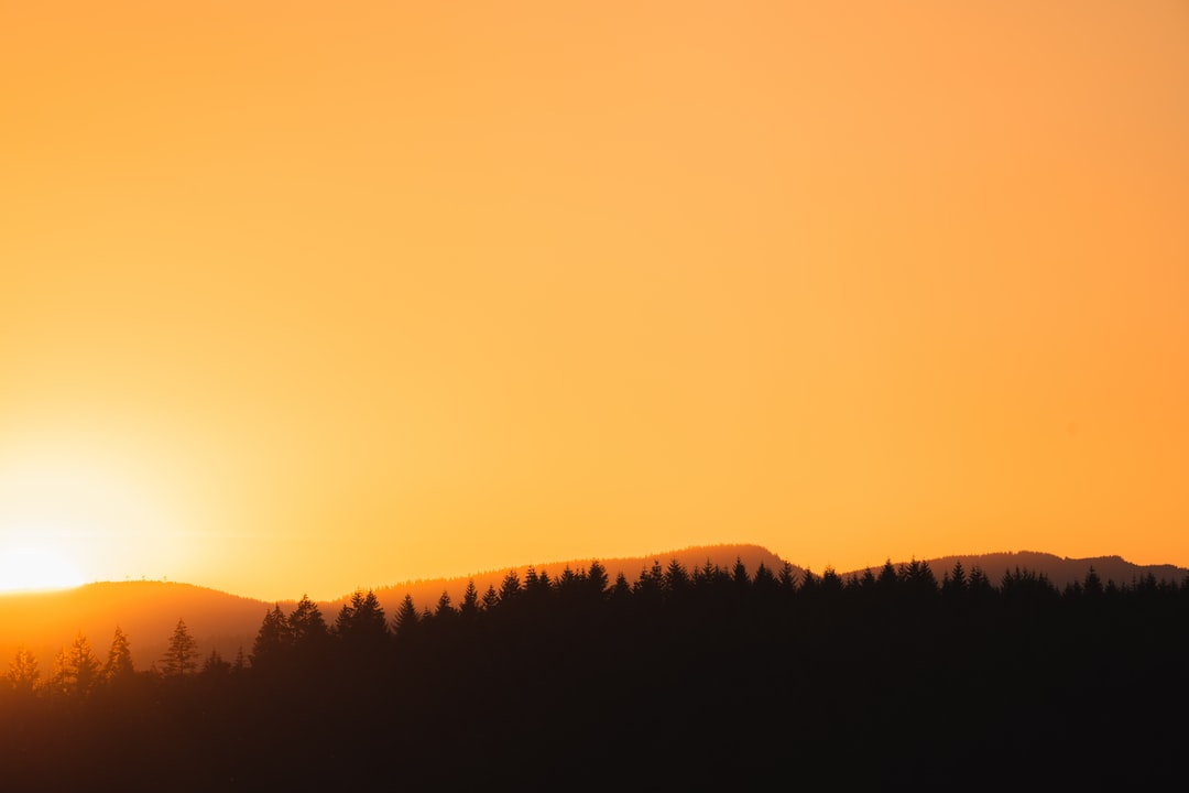 Photograph of the Sun Peeking Over A Distant Mountain - unsplash