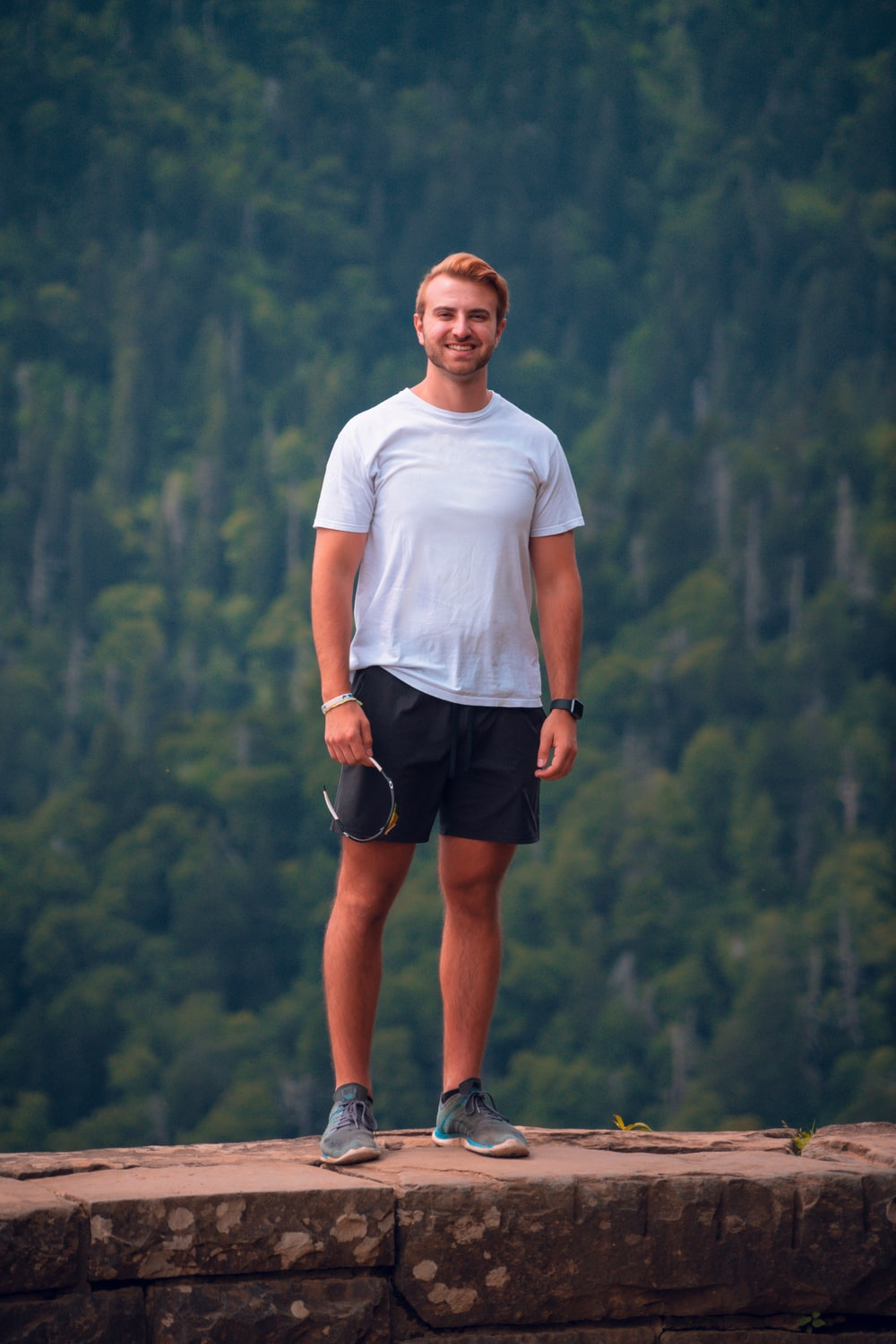 man in white crew neck t-shirt and black shorts standing on mountain during daytime