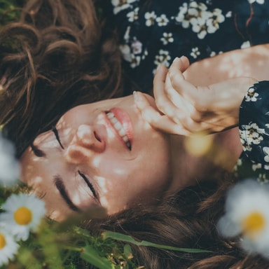 woman in black and white floral shirt lying on green grass field