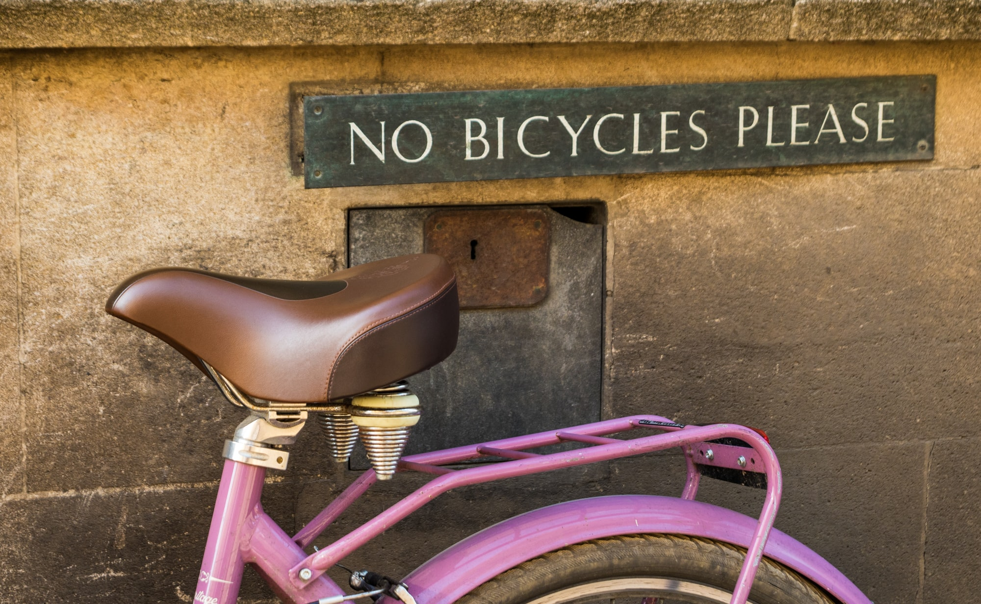 How we love to ignore signs! ;) A n old traditional bicycle parked up in a Cambridge street underneath a No Bicycles sign.