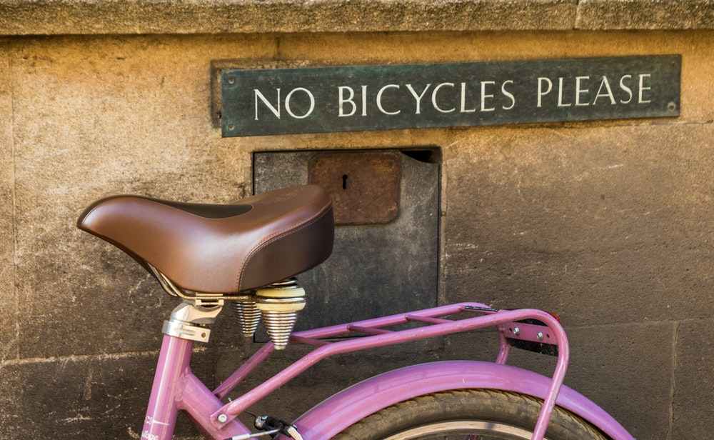 pink bicycle parked beside brown concrete wall