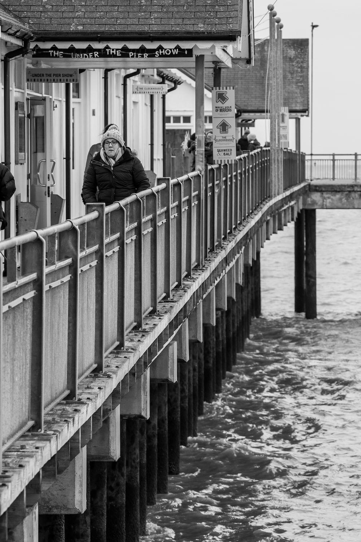 grayscale photo of woman in black jacket standing on bridge