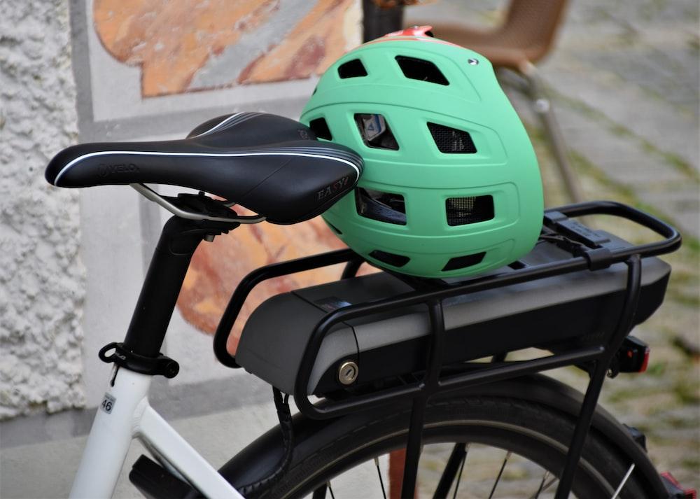 green and black bicycle helmet on bicycle handle bar