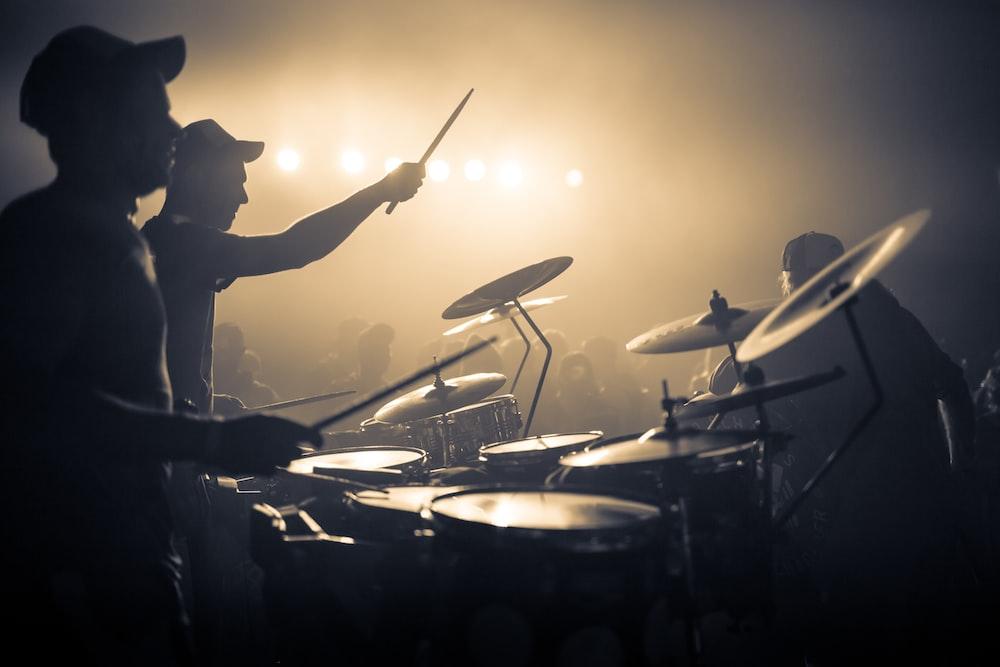 man playing drum with drum sticks