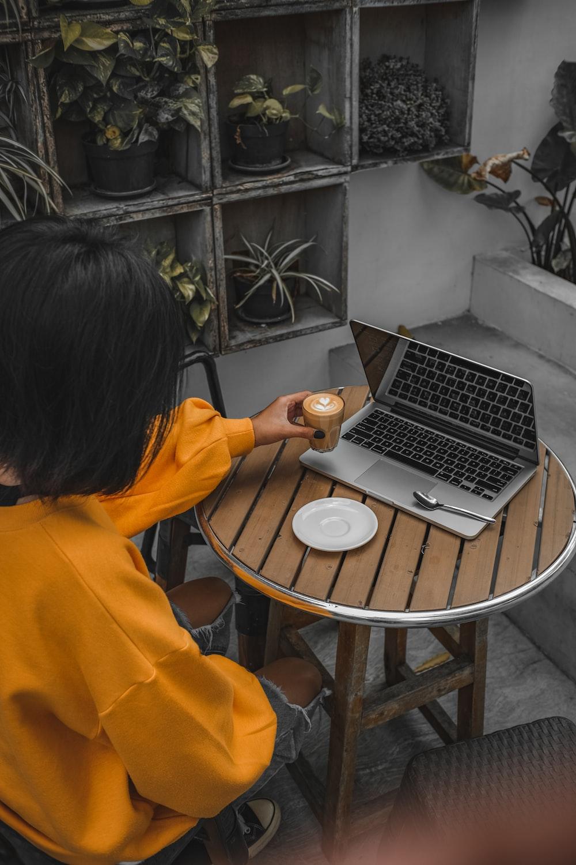 woman in orange hoodie using macbook pro