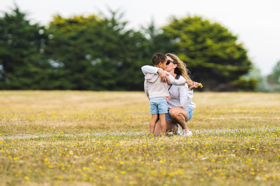 Little Child Offering Flowers To His Mom - unsplash