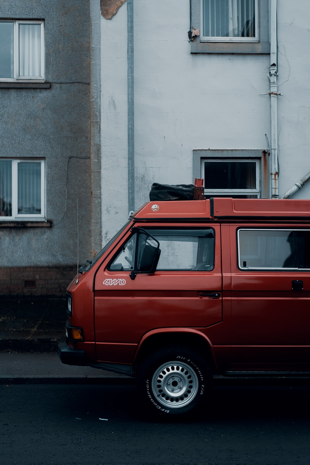 red van parked beside gray concrete building during daytime