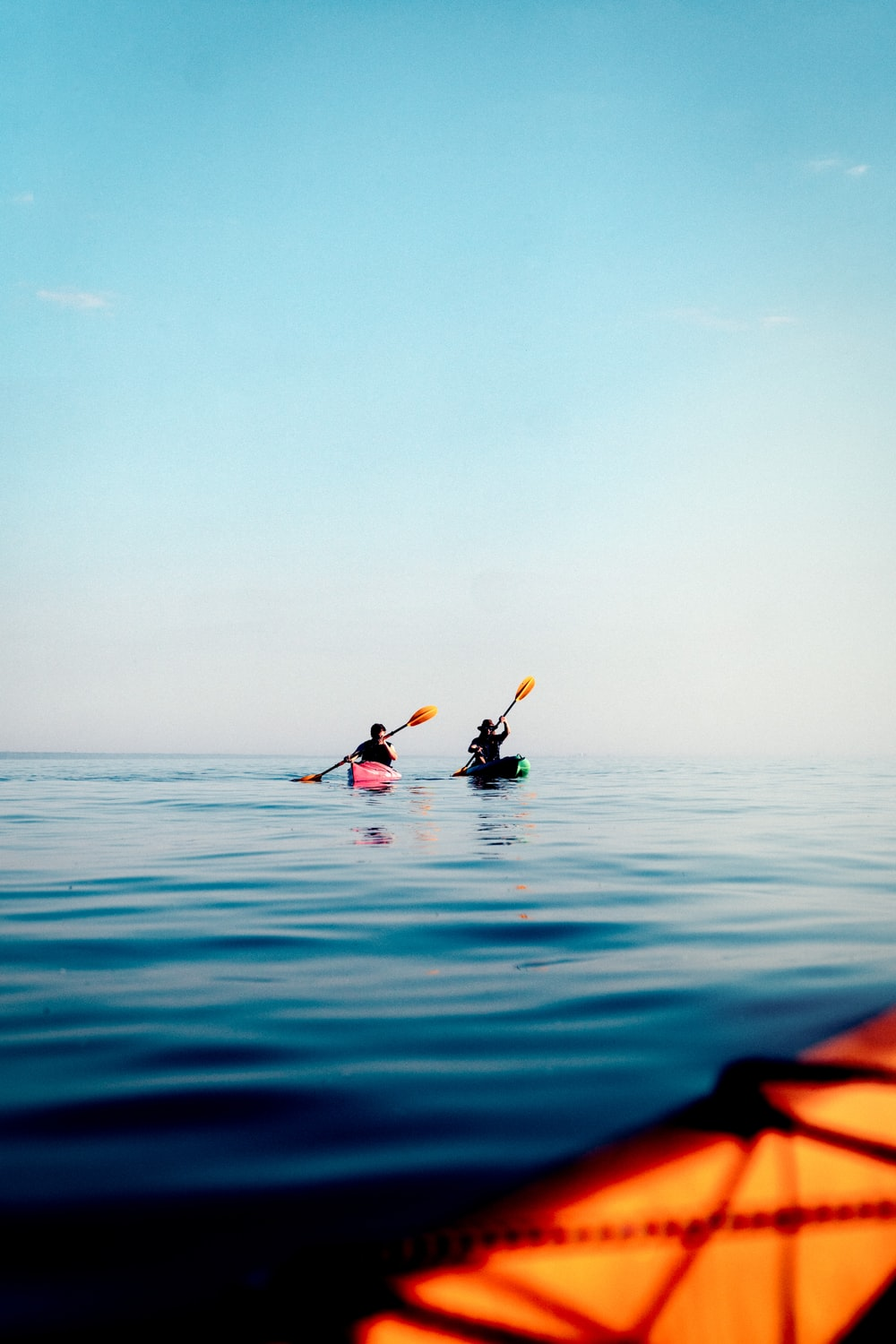 person in black wet suit riding on kayak on blue sea during daytime