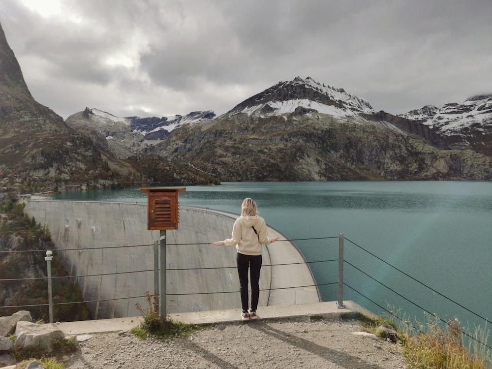 woman in white dress standing on concrete bridge near lake during daytime
