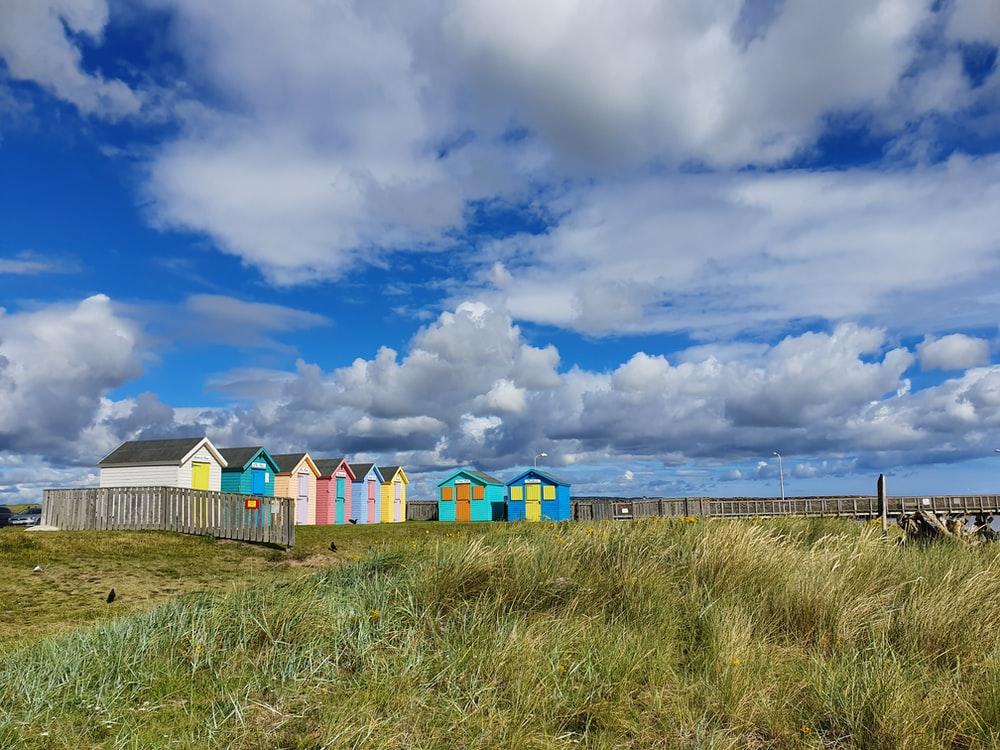 yellow blue and green houses under blue sky during daytime