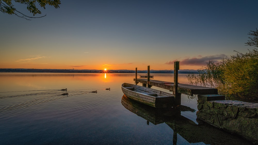 white boat on water during sunset