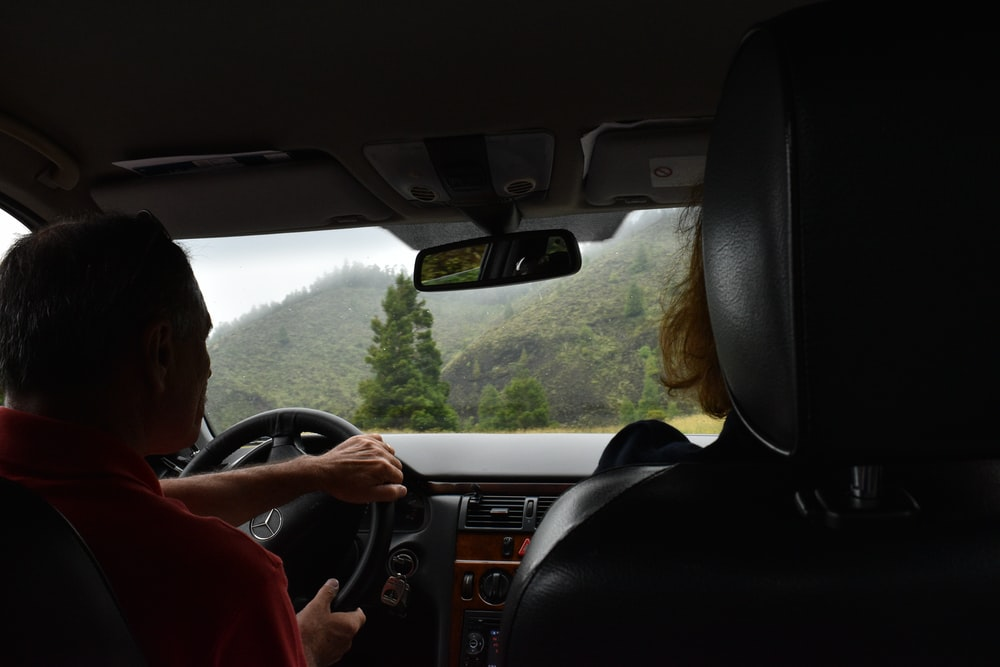 man in red shirt driving car during daytime