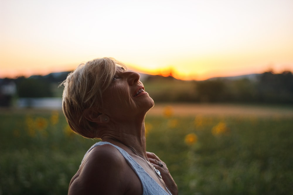 woman in white tank top looking at the sunset