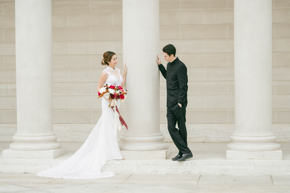 man in black suit and woman in white wedding dress kissing