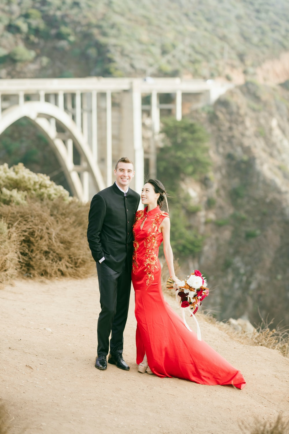 man in black suit and woman in red dress holding bouquet of flowers