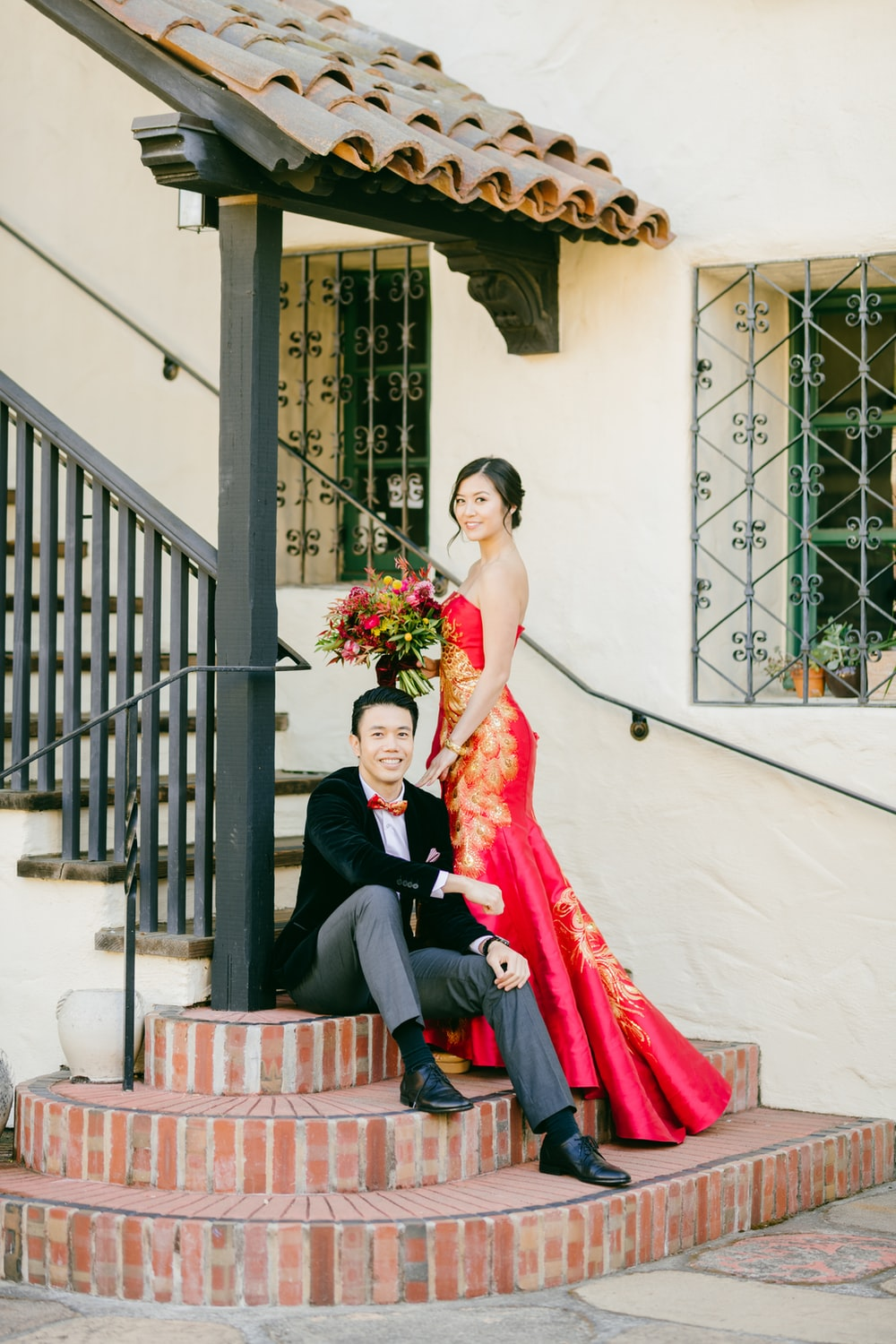 man in black suit jacket and woman in red dress