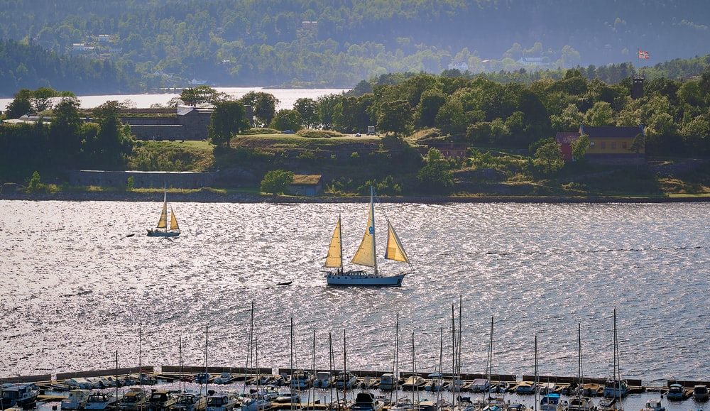 white sail boat on body of water during daytime