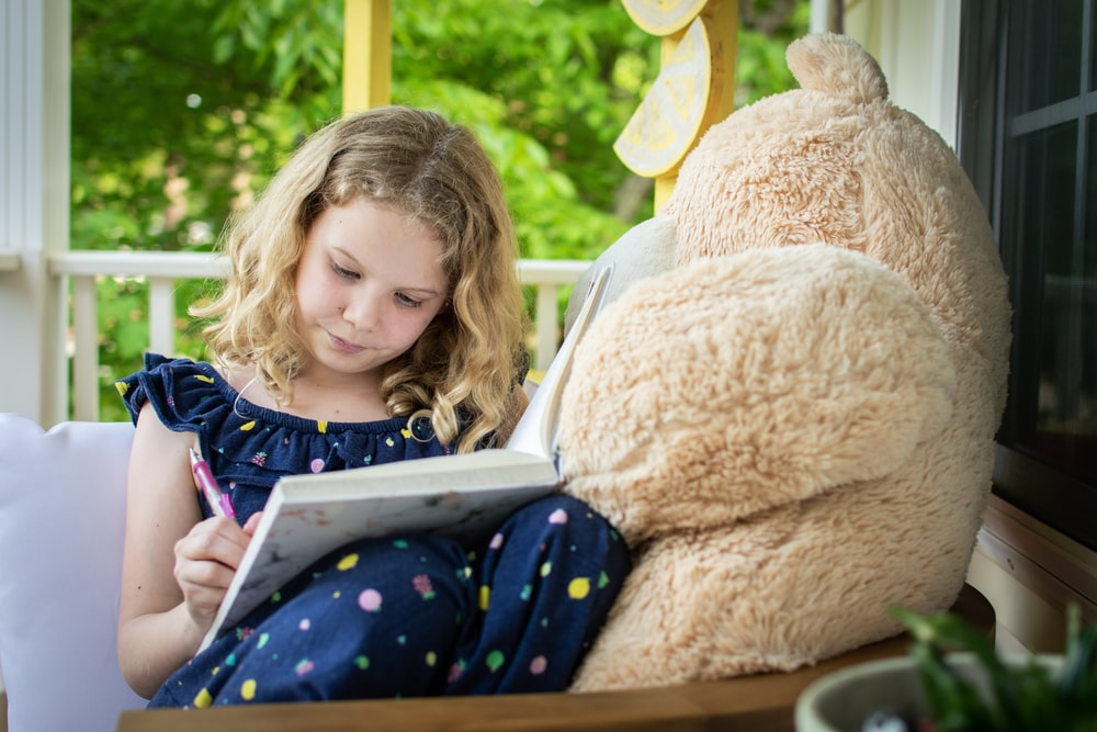 girl in blue and white long sleeve shirt sitting on brown bear plush toy