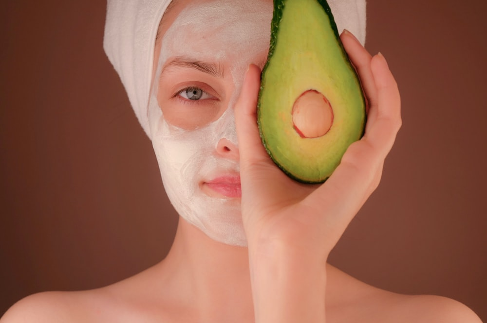 woman with white face mask holding green fruit