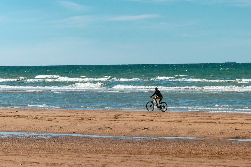 man in black shirt riding bicycle on beach during daytime