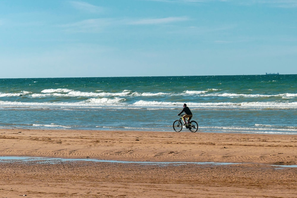 man in black shirt riding bicycle on beach during daytime