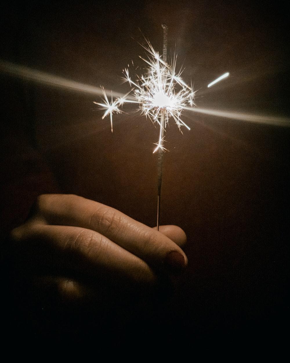 person holding white lighted sparkler