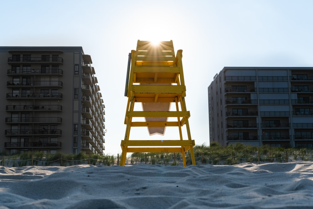 brown wooden chair on white sand near high rise building during daytime