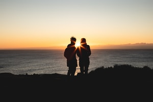 silhouette of man and woman standing on hill during sunset