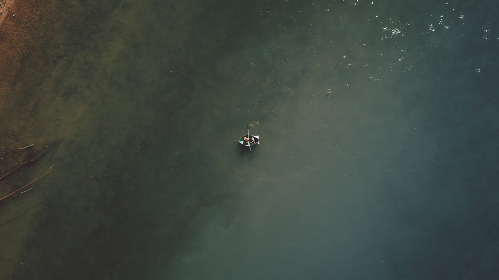 2 people riding on boat on water during daytime