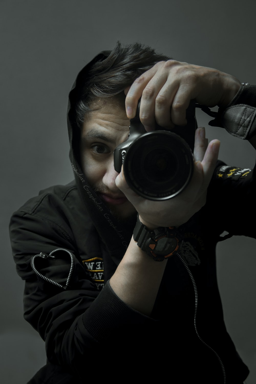 man in black leather jacket holding black dslr camera