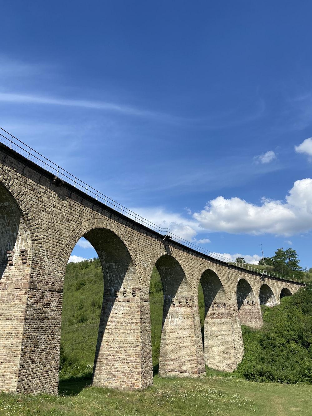 brown concrete bridge under blue sky