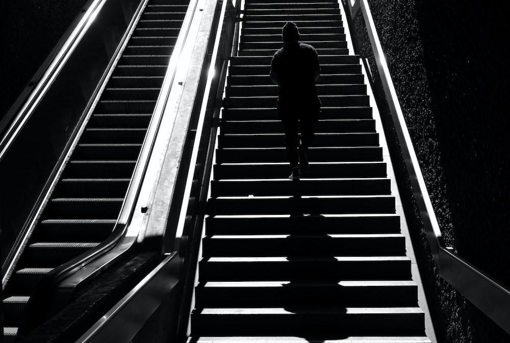 man in black jacket walking on escalator