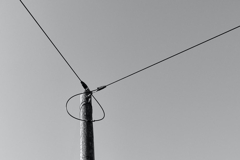 black electric post under gray sky