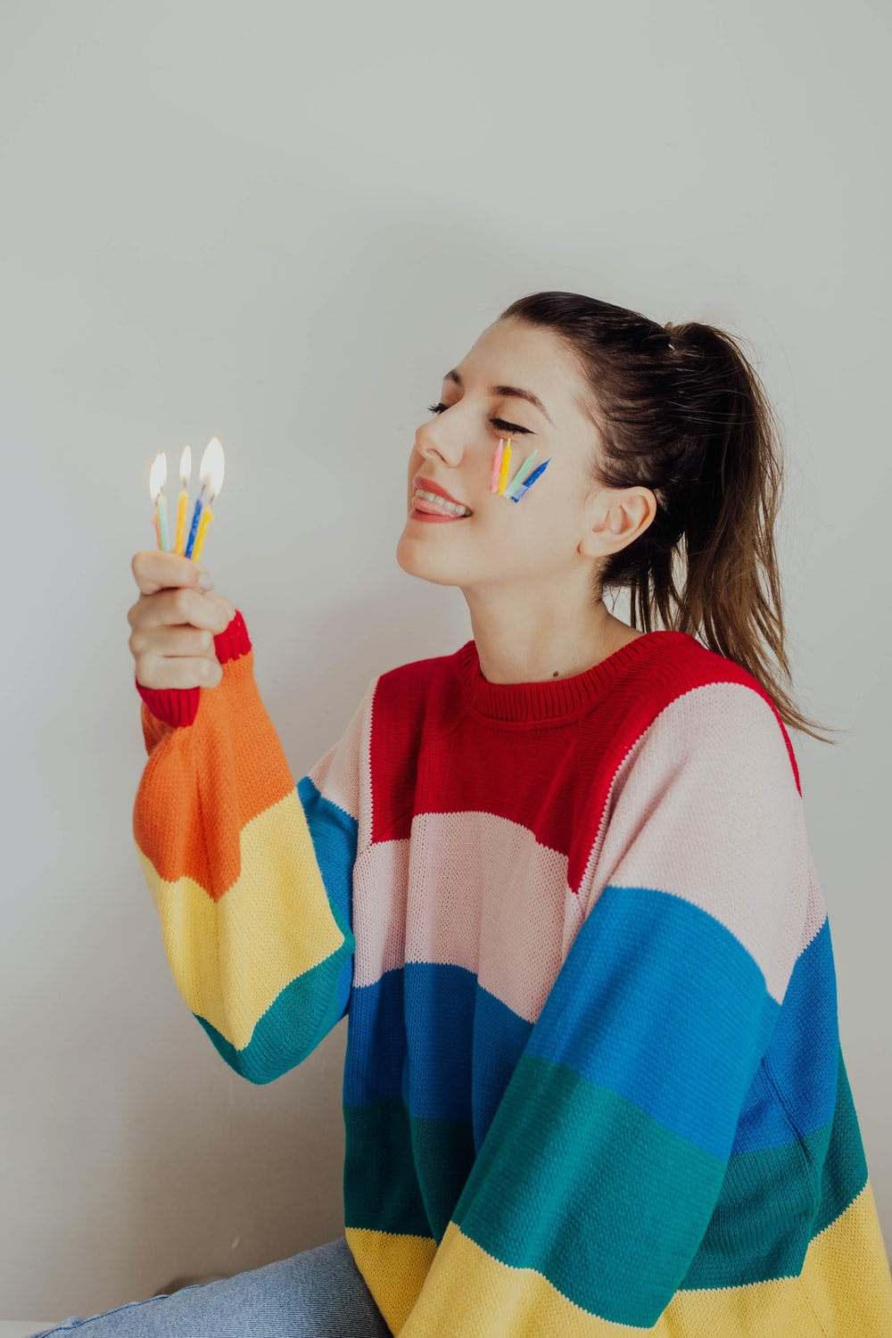 woman in red and blue striped shirt covering her face with multi colored textile