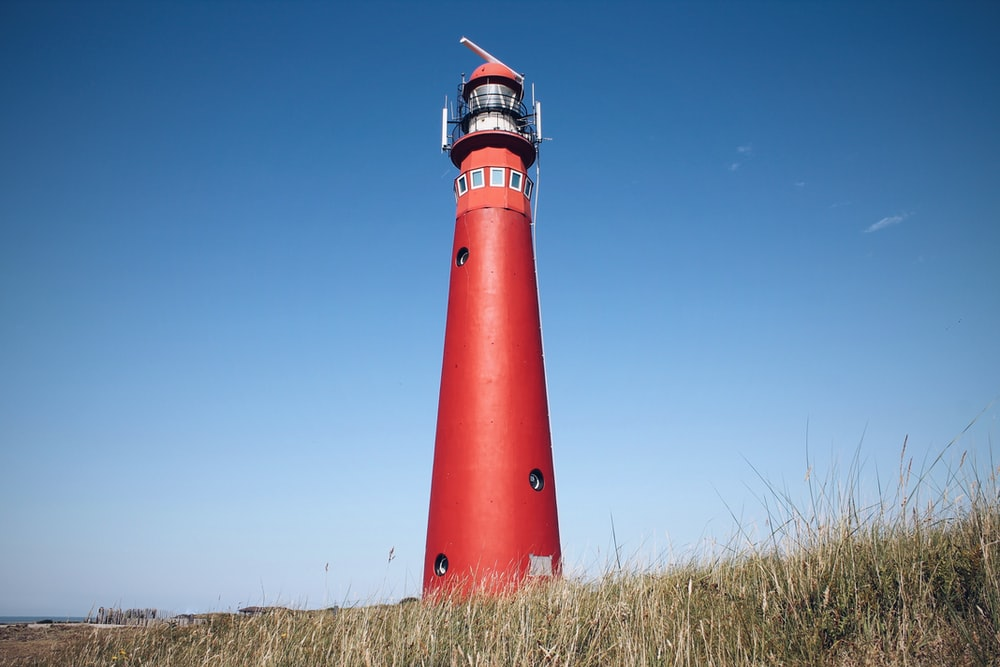 red and white lighthouse under blue sky during daytime