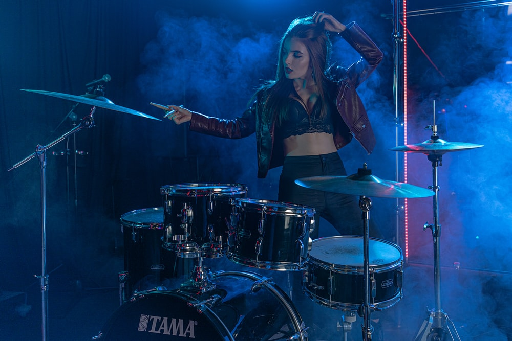 woman in black leather jacket playing drum