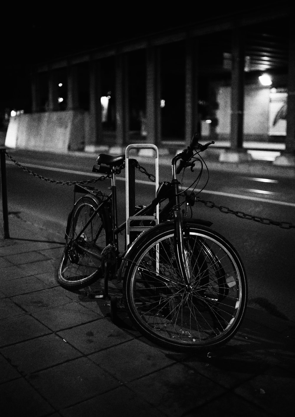 grayscale photo of city bicycle parked beside road