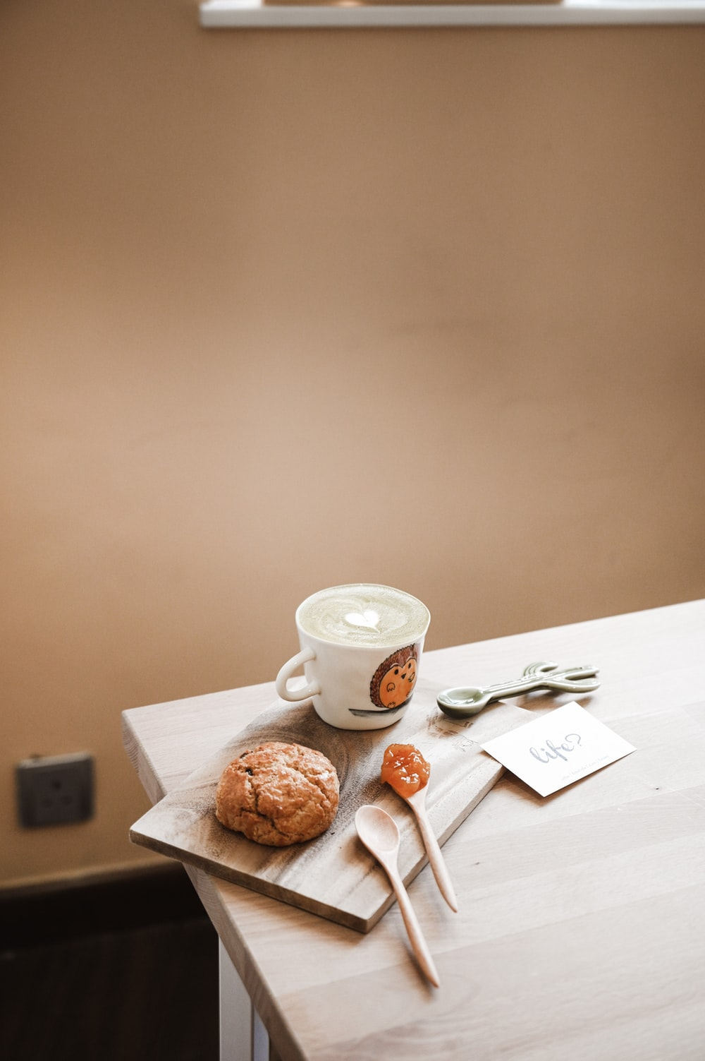 white ceramic teacup on saucer beside bread on table