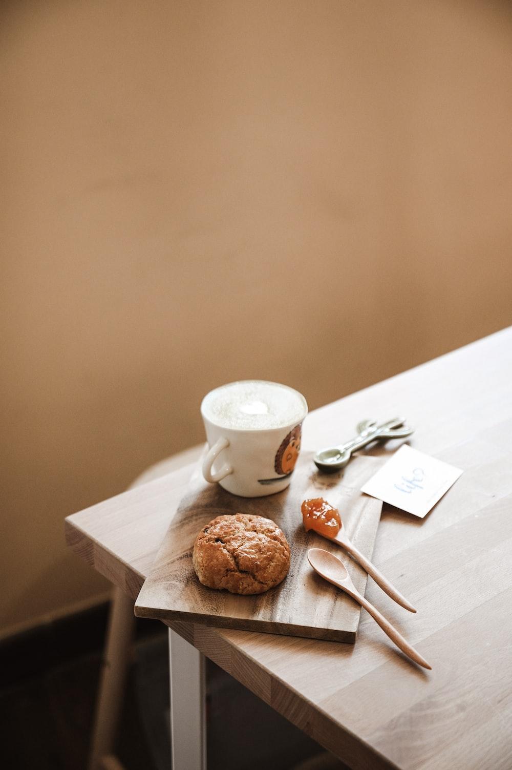 white ceramic mug beside brown bread on white wooden table