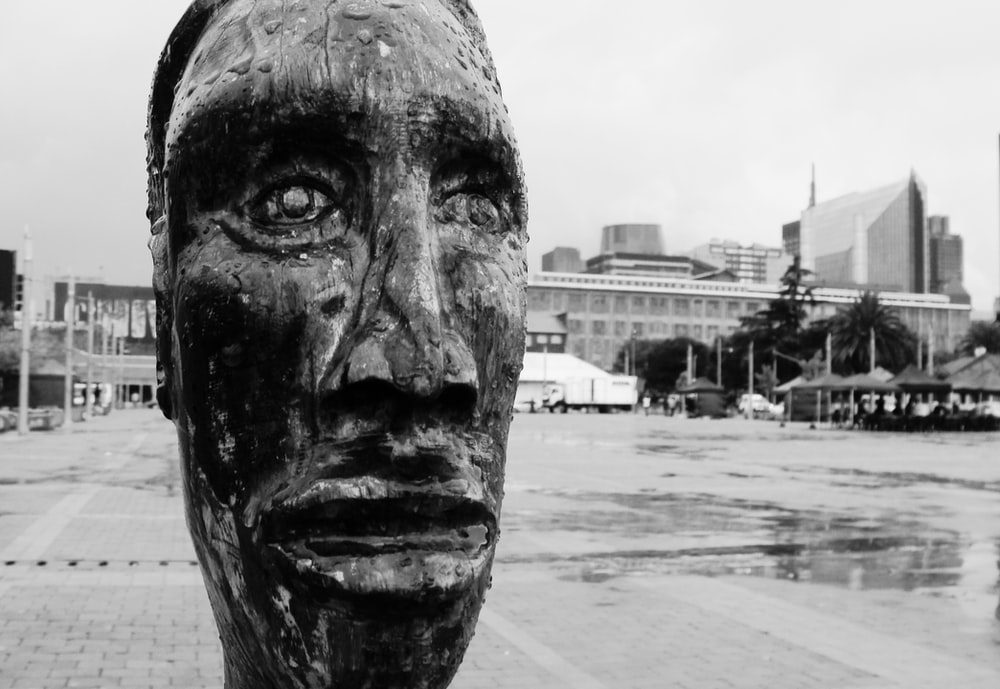 grayscale photo of mans face statue