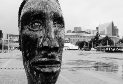 grayscale photo of mans face statue head zoom background