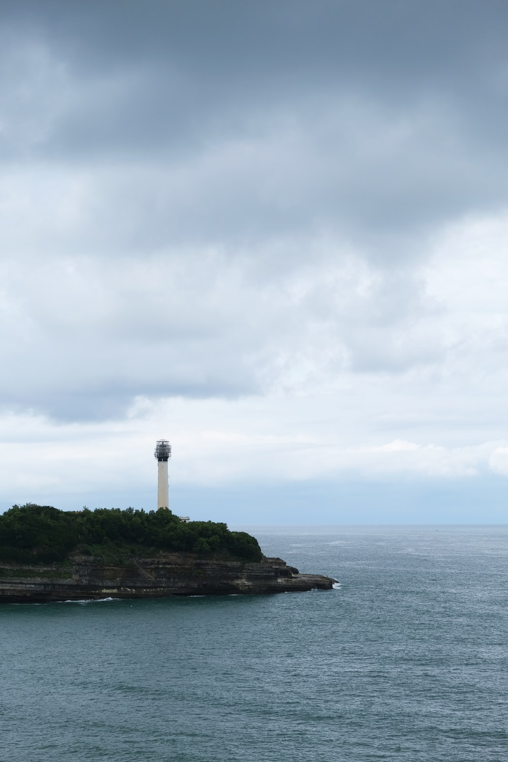white lighthouse on top of green island surrounded by body of water under white clouds during