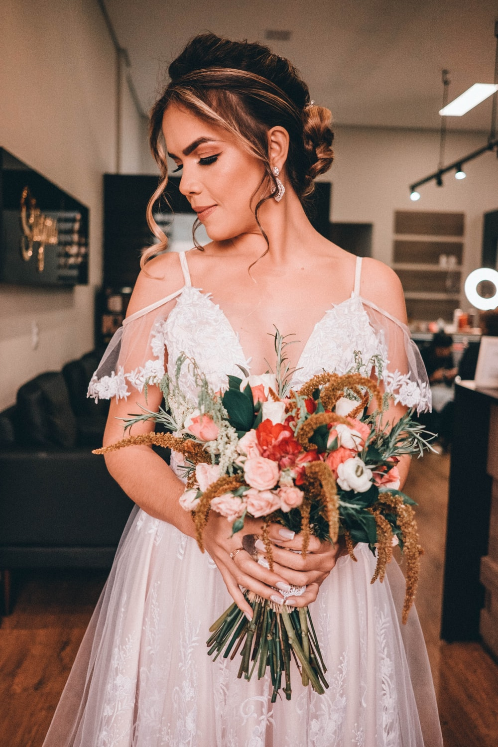 woman in white dress holding bouquet of red roses