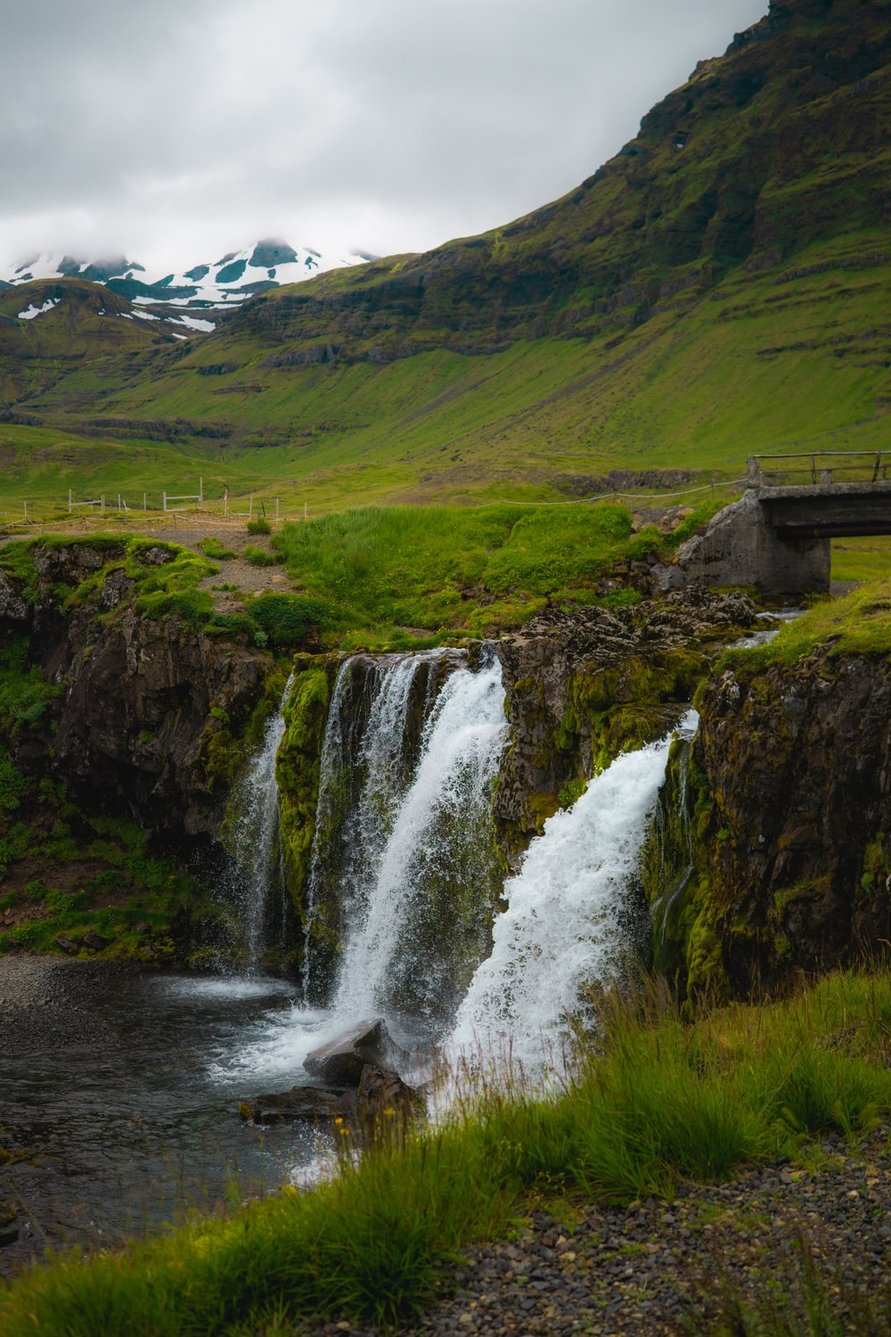waterfalls on green grass covered hill during daytime